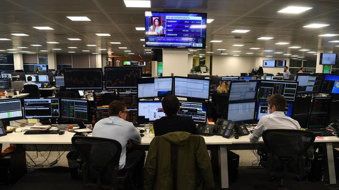 Traders work at the offices of IG markets in the City of London. (AFP)