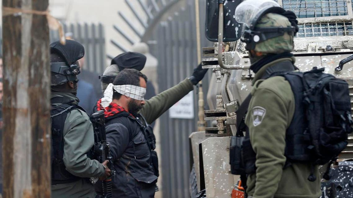 Israeli security forces arrest Palestinian lawyer Tareq Barghout (center, blindfolded) in Ramallah, in the occupied West Bank, on February 27, 2019. (AFP)