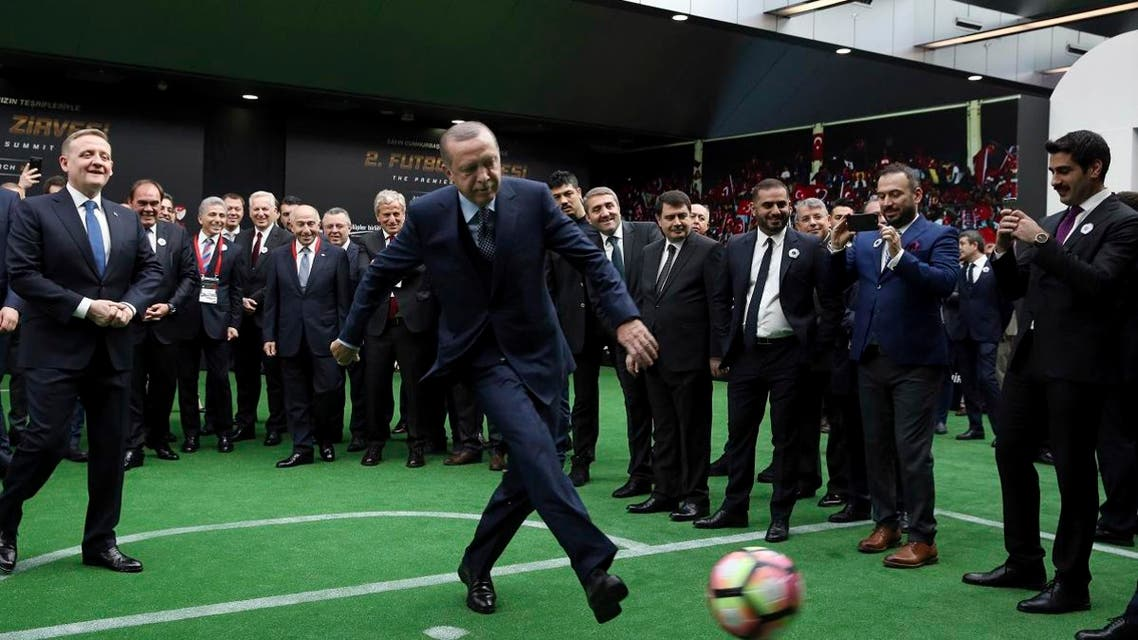 """Turkey's President Recep Tayyip Erdogan kicks a ball, as president of the Turkish Football Federation Yildirim Demiroren (2-L) and others look on during the """"Premiere Summit 2"""" in Istanbul. (AFP)"""