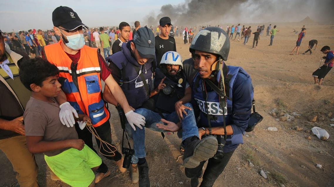 Palestinian paramedics and journalists carry a wounded along the Gaza-Israel border. (AFP)