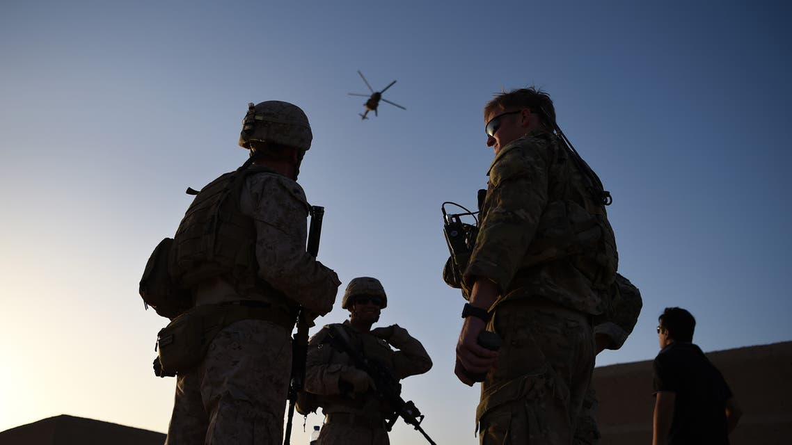 In this photograph taken on August 27, 2017 US Marines and Afghan Commandos stand together as an Afghan Air Force helicopter flies past during a combat training exercise at Shorab Military Camp in Lashkar Gah in Helmand province. Marines in Afghanistan's Helmand say Donald Trump's decision to keep boots on the ground indefinitely gives them all the time in the world to retake the province, once the symbol of US intervention but now a Taliban stronghold. They may need it. At the hot, dusty Camp Shorab, where many of the recently deployed Marines train their Afghan counterparts in flat, desert terrain, the Afghans admit their army still cannot fight alone.