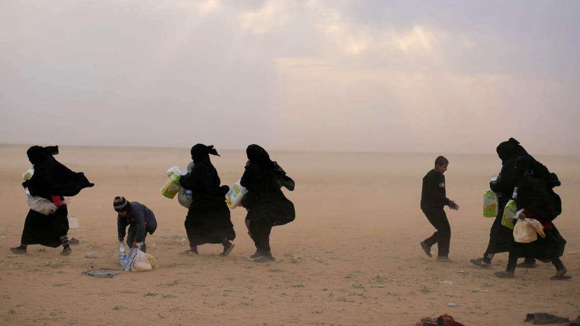 FILE PHOTO: Women walk with their belongings near the village of Baghouz, Deir Al Zor province, Syria February 26, 2019. REUTERS/Rodi Said/File Photo