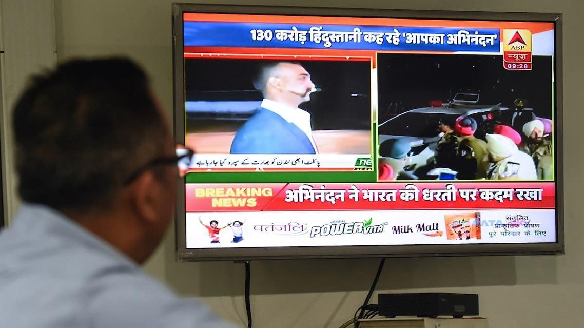An Indian man watches live news channels broadcasting images of Indian Air Force Wing Commander Abhinandan Varthaman returning to India from the India-Pakistan Wagah border in New Delhi on March 1, 2019. (AFP)
