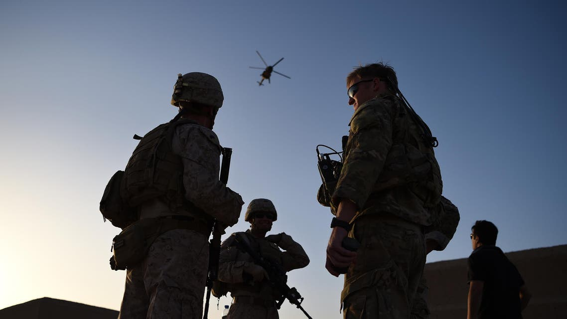 "In this photograph taken on August 27, 2017 US Marines and Afghan Commandos stand together as an Afghan Air Force helicopter flies past during a combat training exercise at Shorab Military Camp in Lashkar Gah in Helmand province. Marines in Afghanistan's Helmand say Donald Trump's decision to keep boots on the ground indefinitely gives them ""all the time in the world"" to retake the province, once the symbol of US intervention but now a Taliban stronghold. They may need it. At the hot, dusty Camp Shorab, where many of the recently deployed Marines train their Afghan counterparts in flat, desert terrain, the Afghans admit their army still cannot fight alone."