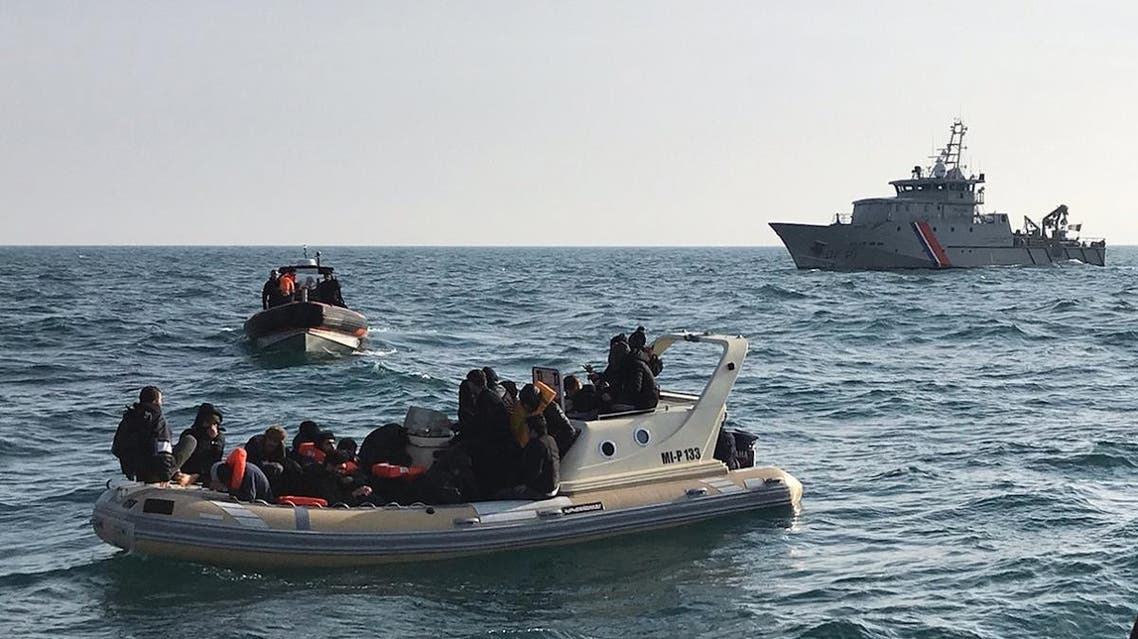 British rescuers (front) helping some 20 migrants on a semi-rigid boat trying make their way from France across the English Channel. (AFP)