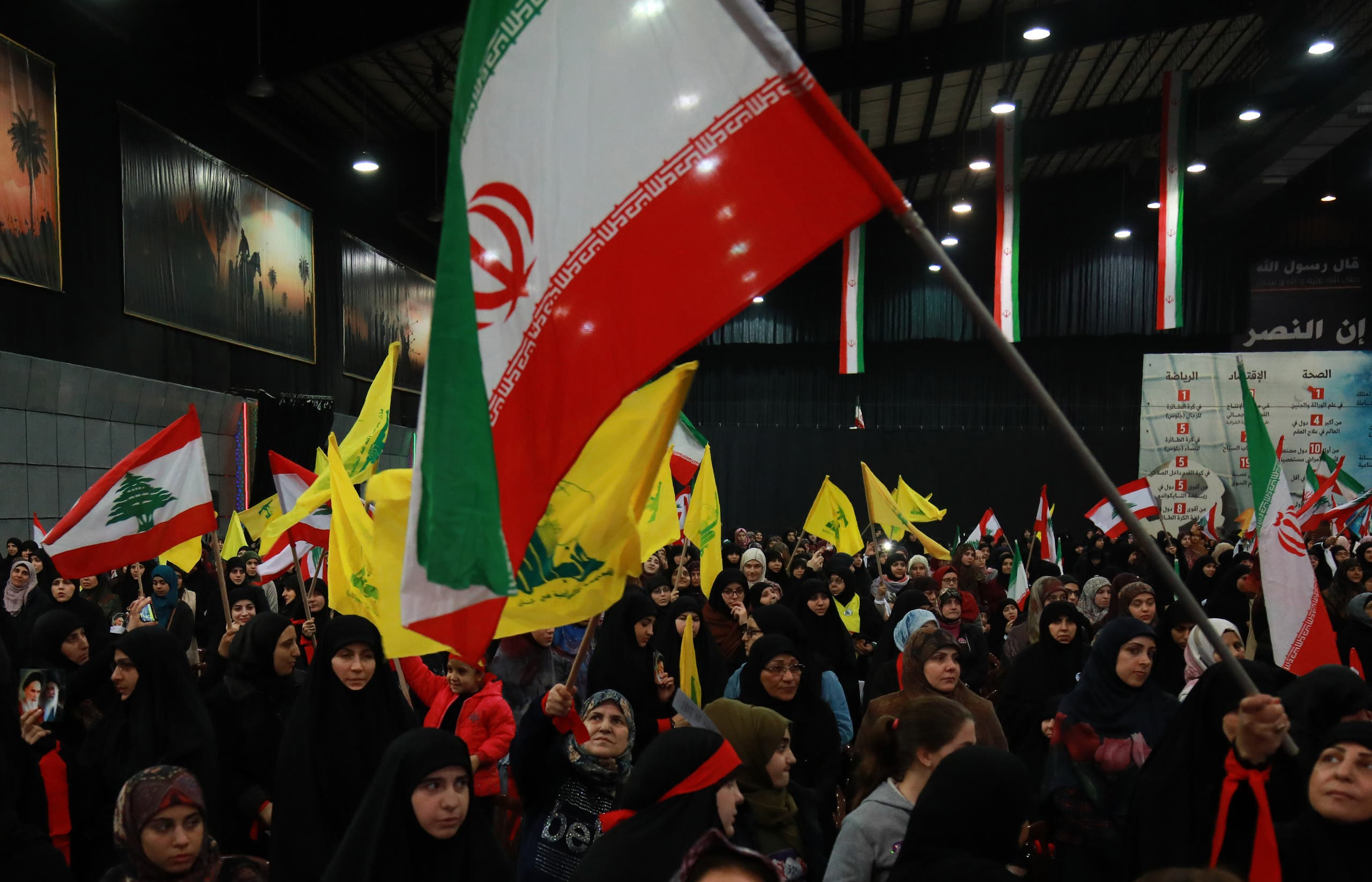 Supporters of Lebanese Hezbollah wave the movement's yellow flag along with Iran's flag during celebrations marking the 40th anniversary of the Iranian revolution in the capital Beirut's southern suburbs on February 6, 2019.