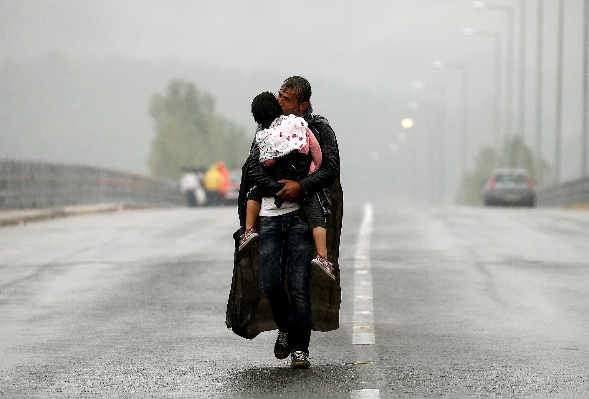 A Syrian refugee kisses his daughter as he walks through a rainstorm towards Greece's border with Macedonia on September 10, 2015. (Reuters/ Yannis Behrakis)