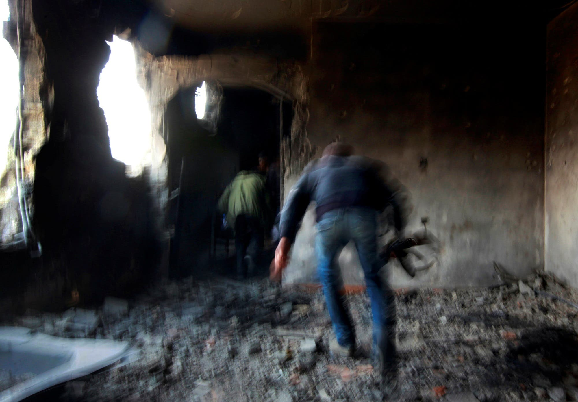 Rebel fighters run for cover inside a building on the frontline in Tripoli street in central Misrata, April 21, 2011. (Reuters/ Yannis Behrakis)