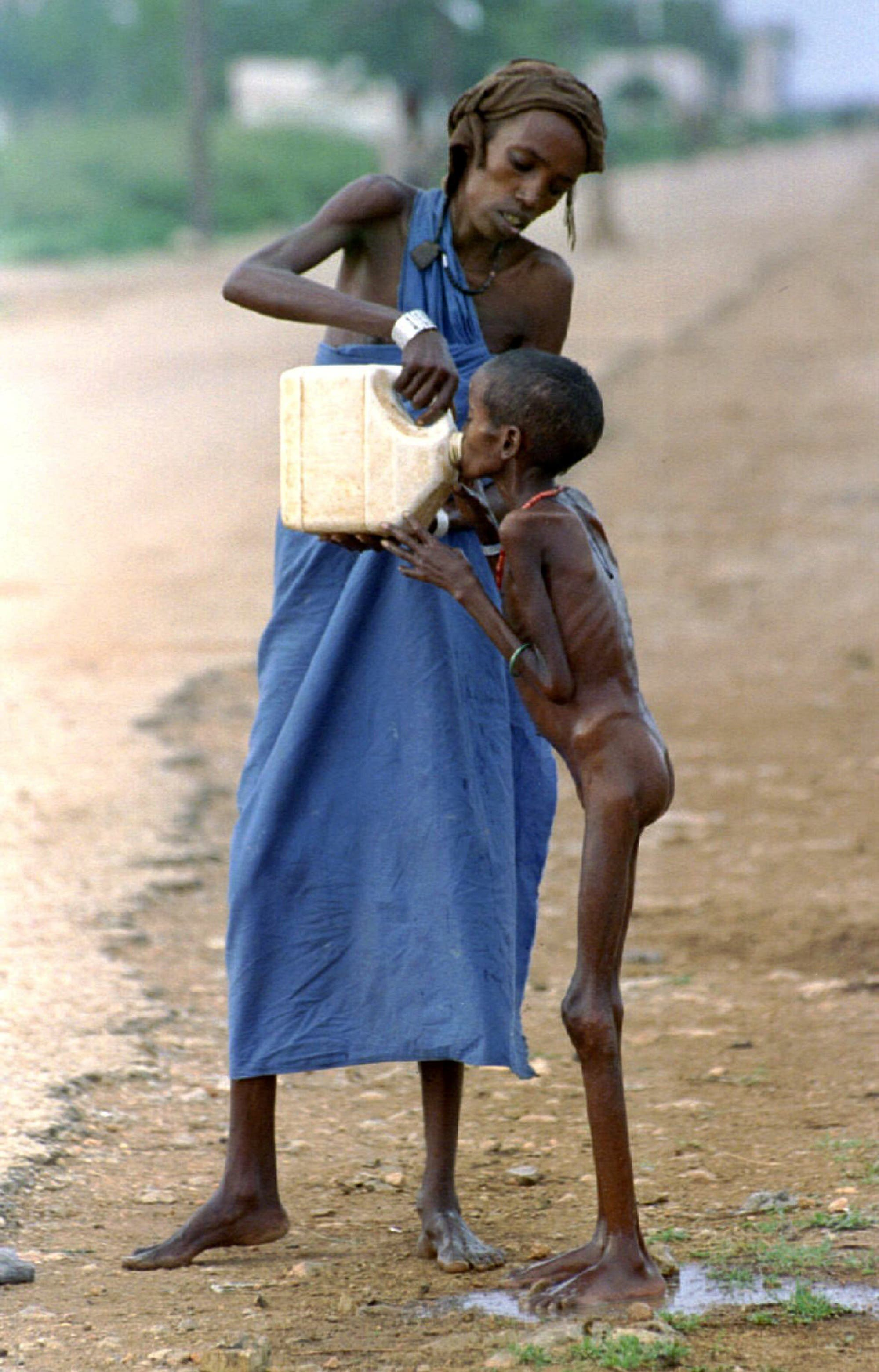 A starving Somali child is given water near a refugee camp in Baidoa, Somalia, on December 14, 1992. (Reuters/ Yannis Behrakis)