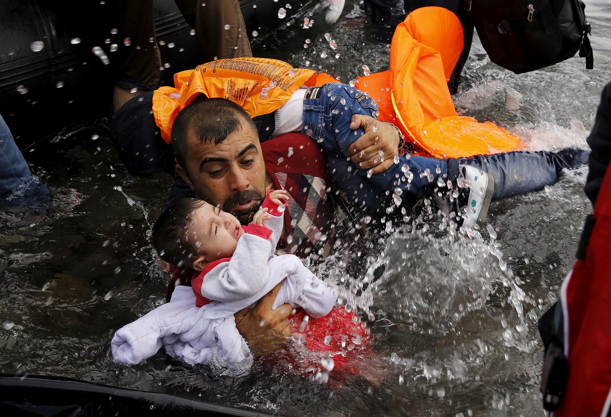 A Syrian refugee holds onto his children as he struggles to walk off a dinghy on the Greek island of Lesbos, on September 24, 2015. (Reuters/ Yannis Behrakis)