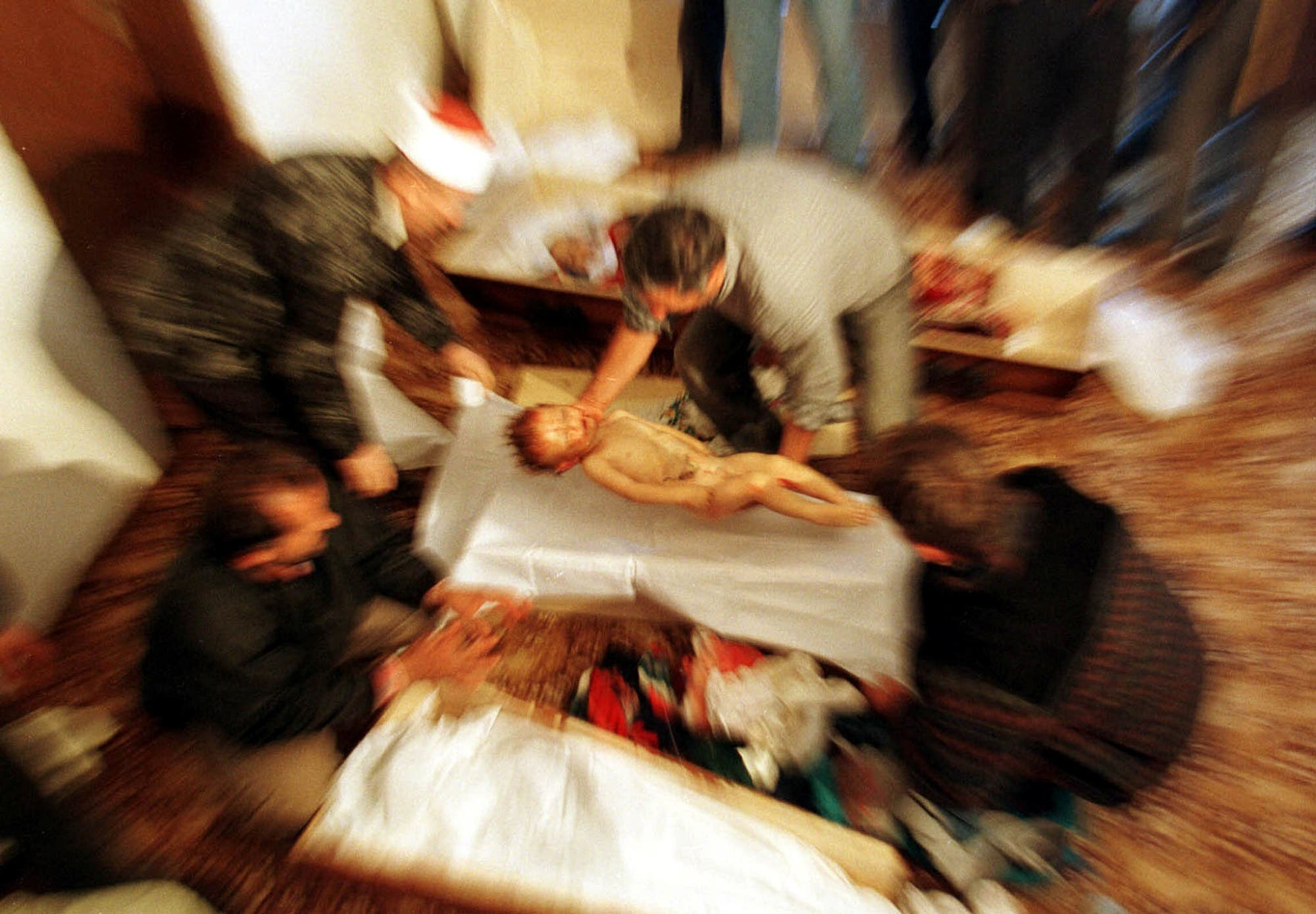 An ethnic Albanian man places the body of two-year-old Mozzlum Sylmetaj into a coffin next to the coffins of three other family members killed by Yugoslav army troops. (Reuters/ Yannis Behrakis)