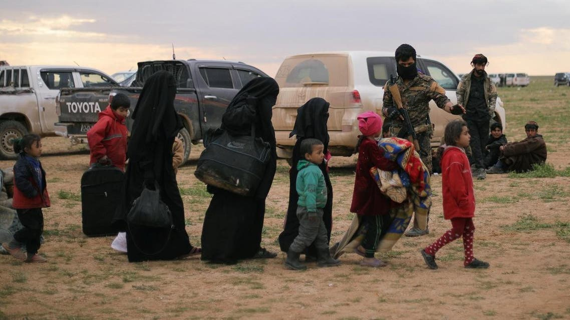 Women walk with children near the village of Baghouz, Deir Al Zor province. (Reuters)