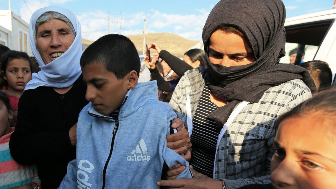 طفل إيزيدي بين أقاربه بعد تحريره من داعش في سوريا(2/3/2019- رويترز)