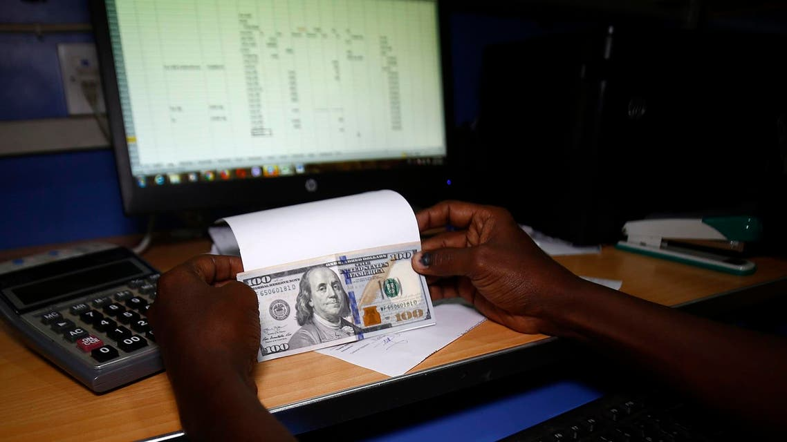 vAn employee shows US dollar banknotes at a foreign currency brokerage office in Khartoum on October 7, 2018. (AFP)