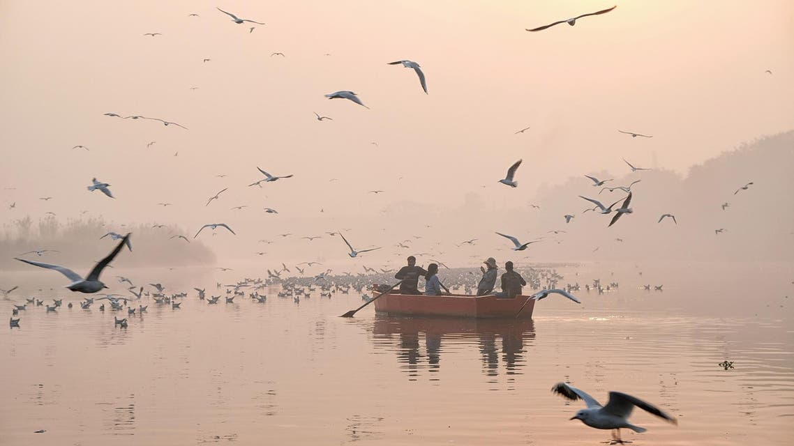 Indian women take pictures on a boat as migratory birds fly overhead on a morning of heavy air pollution in New Delhi on November 20, 2018. (AFP)