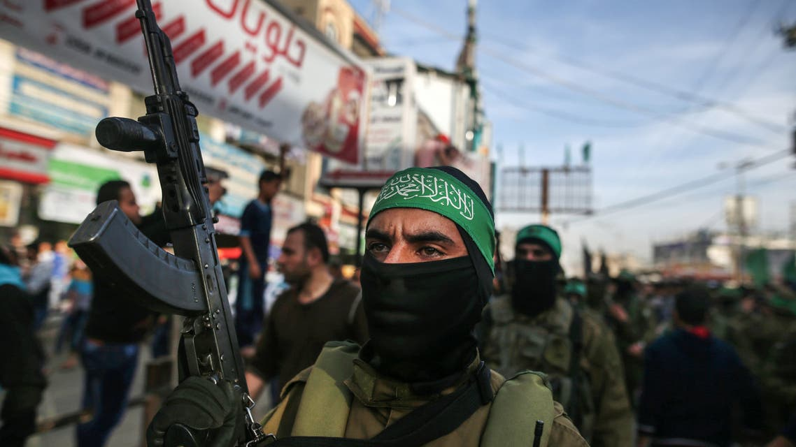 A member of Hamas' armed wing al-Qassam Brigades stands guard carrying a Kalashnikov assault rifle during the funeral of Ziad al-Howajri, one of the members of Hamas' security forces, in al-Nusairat refugee camp in the central Gaza Strip on March 22, 2018, after he was killed with a comrade while attempting to arrest a suspect in a bomb attack against the Palestinian prime minister during his visit to the enclave on March 13.