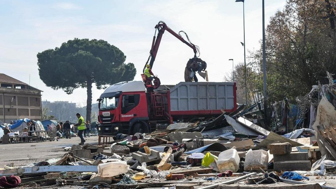 A crate truck picks remains of belongings dring the eviction of a makeshift migrants' camp by police forces in Rome. (File photo: AFP)