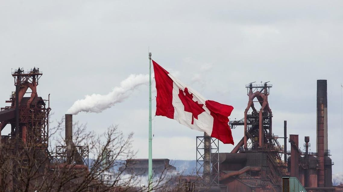 A Canadian flag flies above another industry site with ArcelorMittal Dofasco in the background in Hamilton, Ontario. (Reuters)