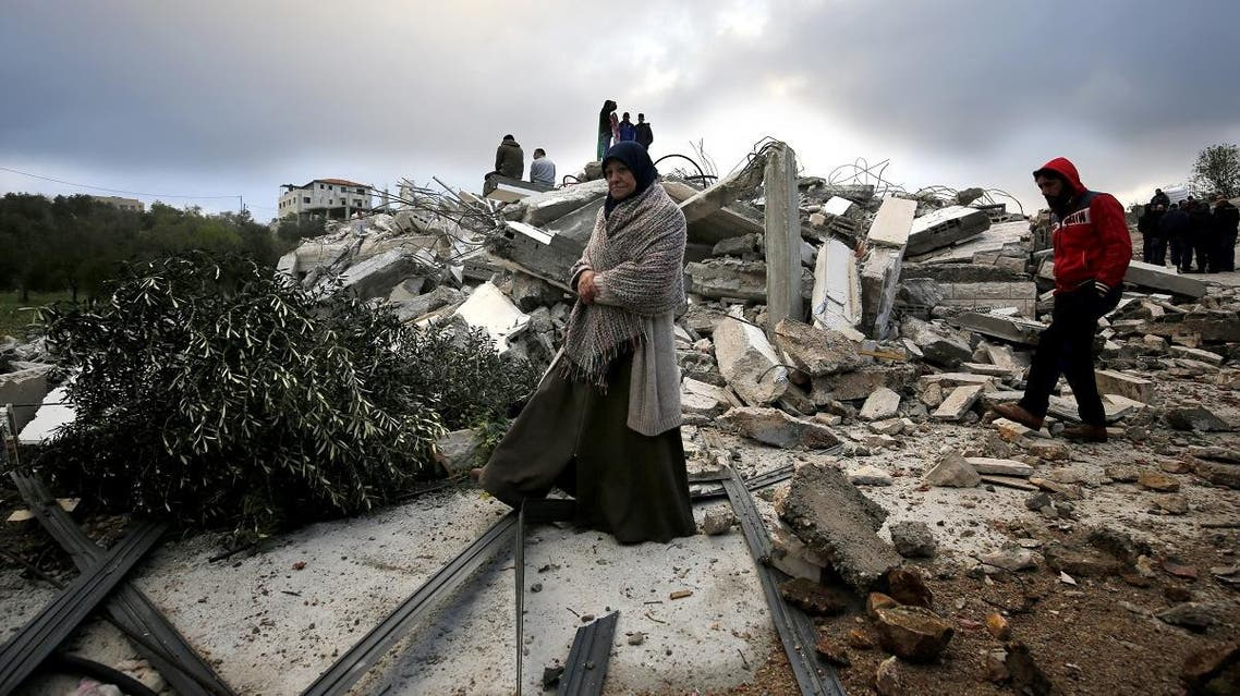 The mother of Palestinian Assam Barghouti, checks the rubble of the family house after it was demolished by Israeli forces. (AFP)