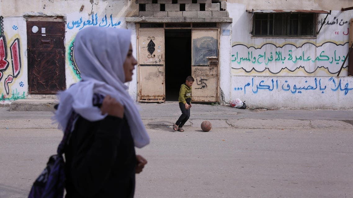 A boy plays with a ball as Palestinian high school student Wessal Abu Amra, 17, walks home from school, in Gaza City, February 14, 2019 (reuters)