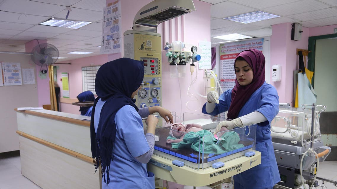 Palestinian midwife Sara Abu Taqea (R), 23, who works in the maternity ward at Gaza's Al-Ahli hospital, weighs a newborn at the hospital in Gaza City (reuters)