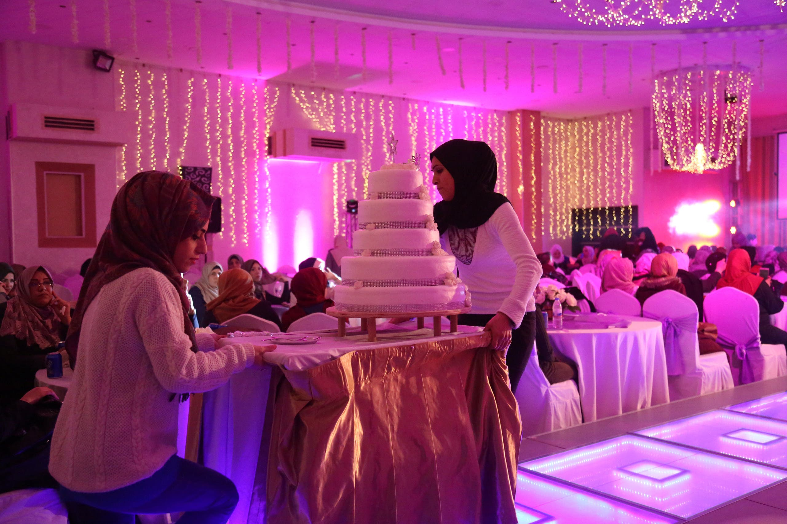 Palestinian Sahar Yaghi (L), 28, prepares to serve cake during a wedding party at a hotel in Gaza City (reuters)