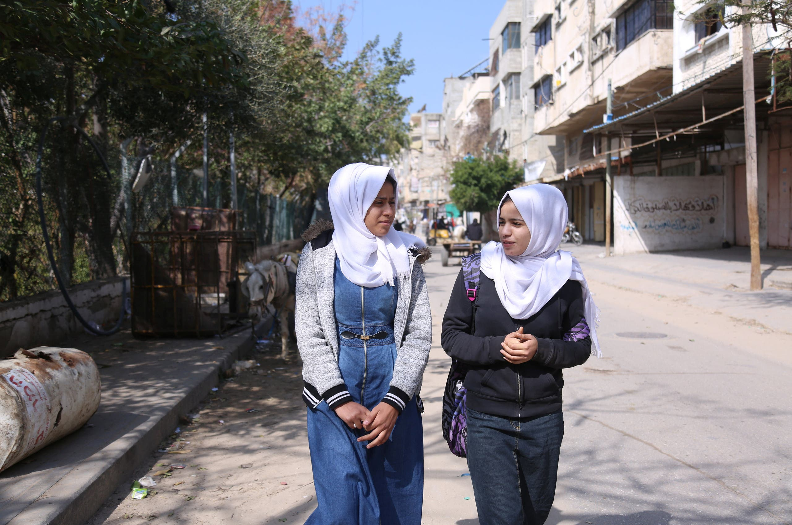 Palestinian high school student Wessal Abu Amra (R), 17, walks home from school with her colleague, in Gaza City. (File photo: Reuters)