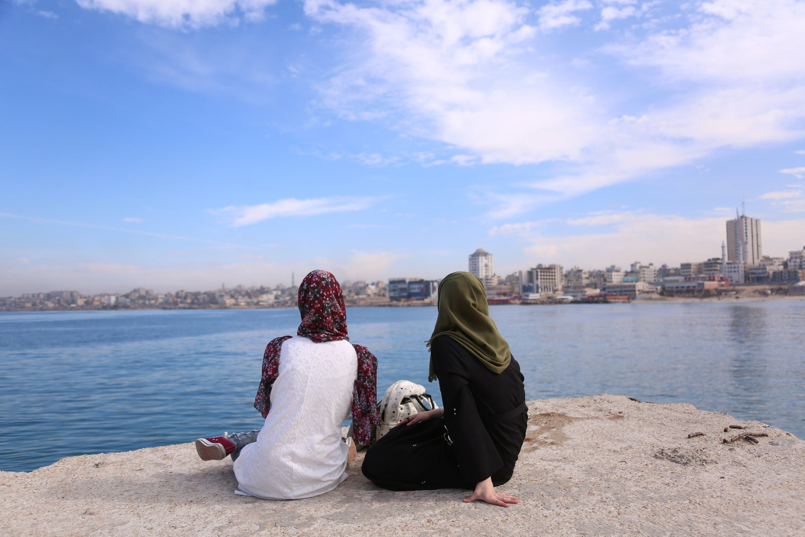 Palestinian Sara Abu Taqea (R), 23, who works in the maternity ward at Gaza's Al-Ahli hospital, and her friend spend time at the seaport in Gaza City (reuters)