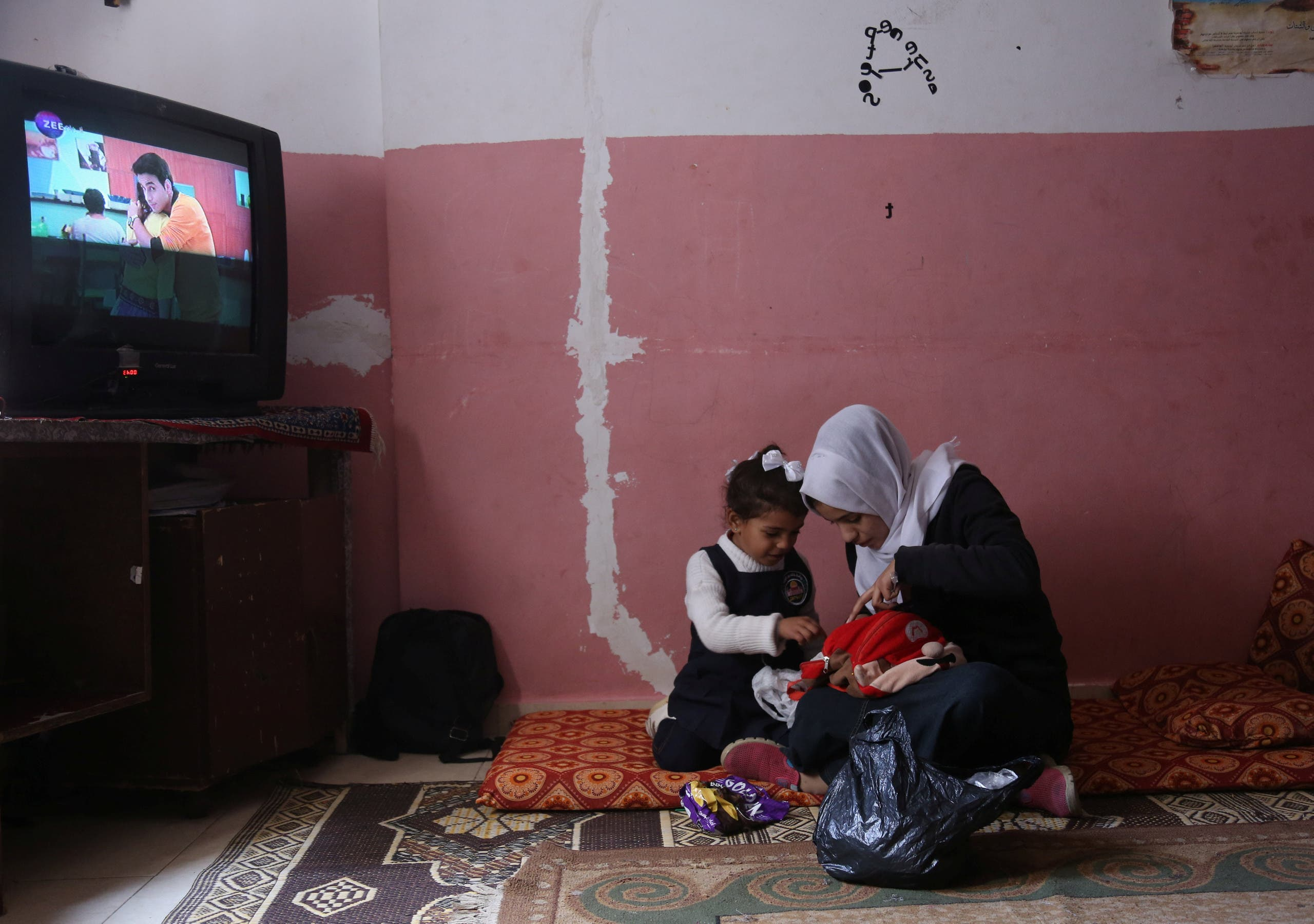 Palestinian high school student Wessal Abu Amra, 17, plays with her sister in their family house, in Gaza City. (File photo: Reuters)