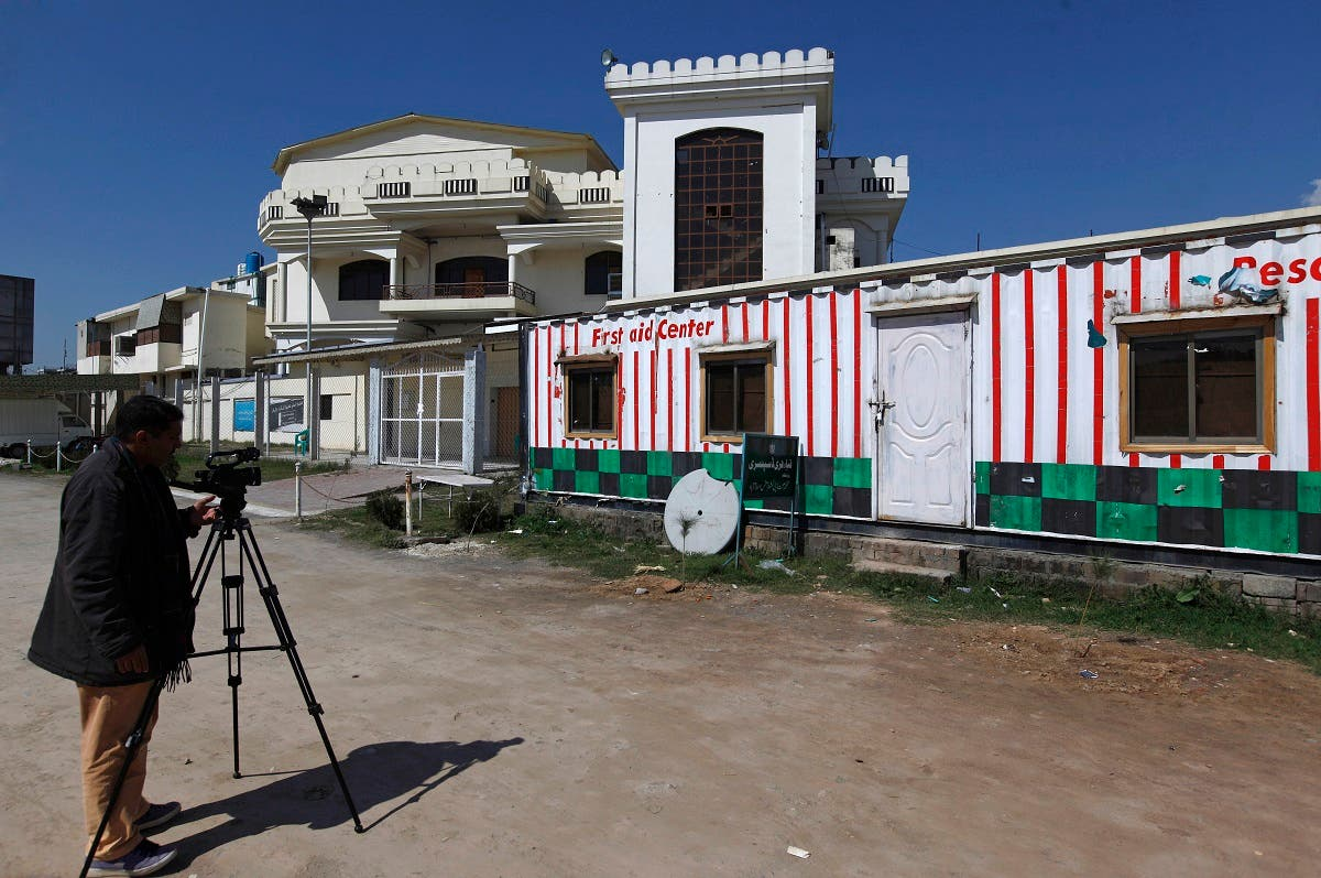 A Pakistani cameraman films a school and dispensary sealed by authorities beside a mosque belong to a banned religious group, in Islamabad, Pakistan, Wednesday, March 6, 2019.