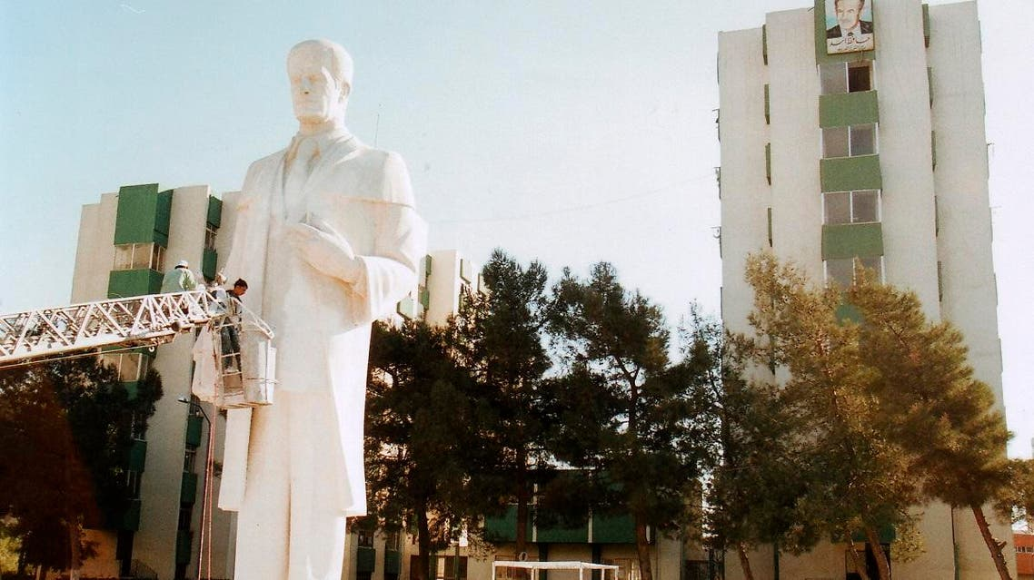 A file photo showing workers installing a statue of Syria's former president Hafez al-Assad at the University of Damascus. (AP)