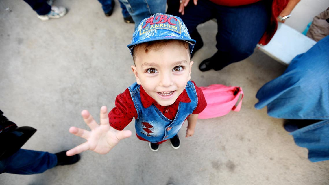 Syrian child Luay smiles before boarding a bus with his family on September 17, 2018 as they return to Syria after living as refugees in Lebanon for years. (AFP)