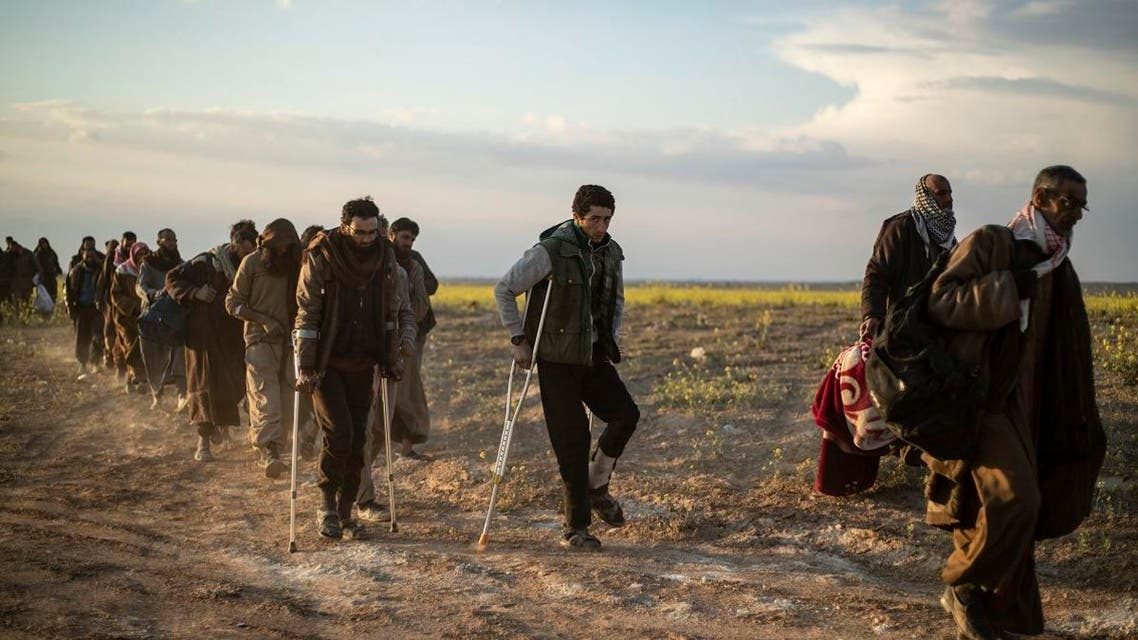 Men suspected of being ISIS fighters walk together toward a screening point for new arrivals run by US-backed Syrian Democratic Forces outside Baghouz in the eastern Syrian Deir Ezzor province on March 6, 2019. (AFP)