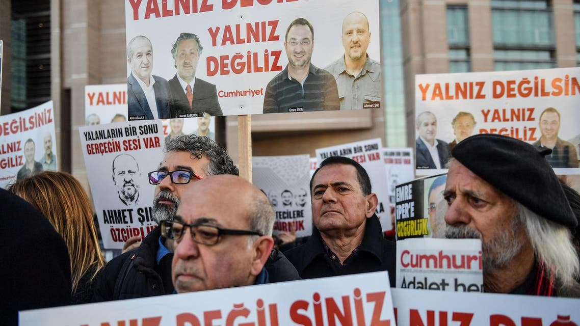 Protestors hold placards with images of jailed journalists in Istanbul on December 25, 2017. (AFP)