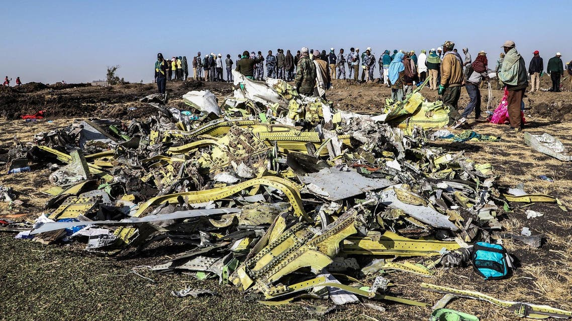 People stand near collected debris at the crash site of Ethiopia Airlines near Bishoftu on March 11, 2019. (AFP)