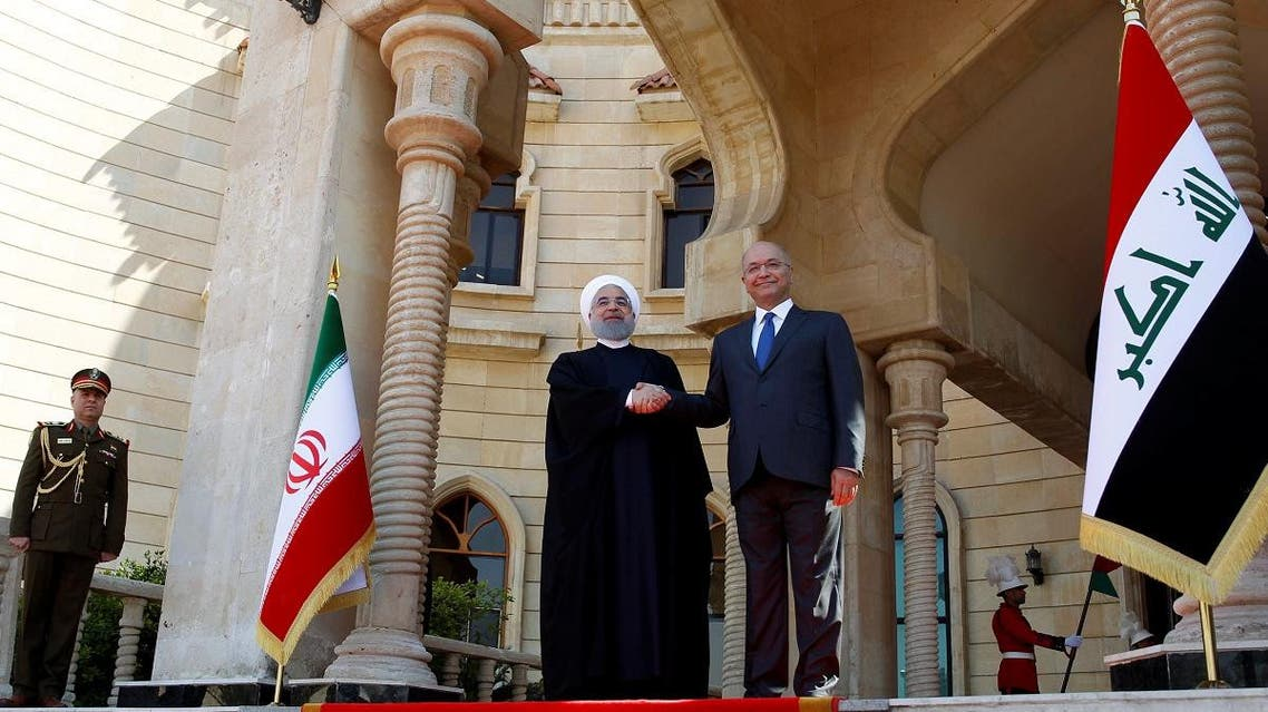 Iraq's President Barham Salih shakes hands with Iranian President Hassan Rouhani during a welcome ceremony at Salam Palace in Baghdad, March 11, 2019. (Reuters)