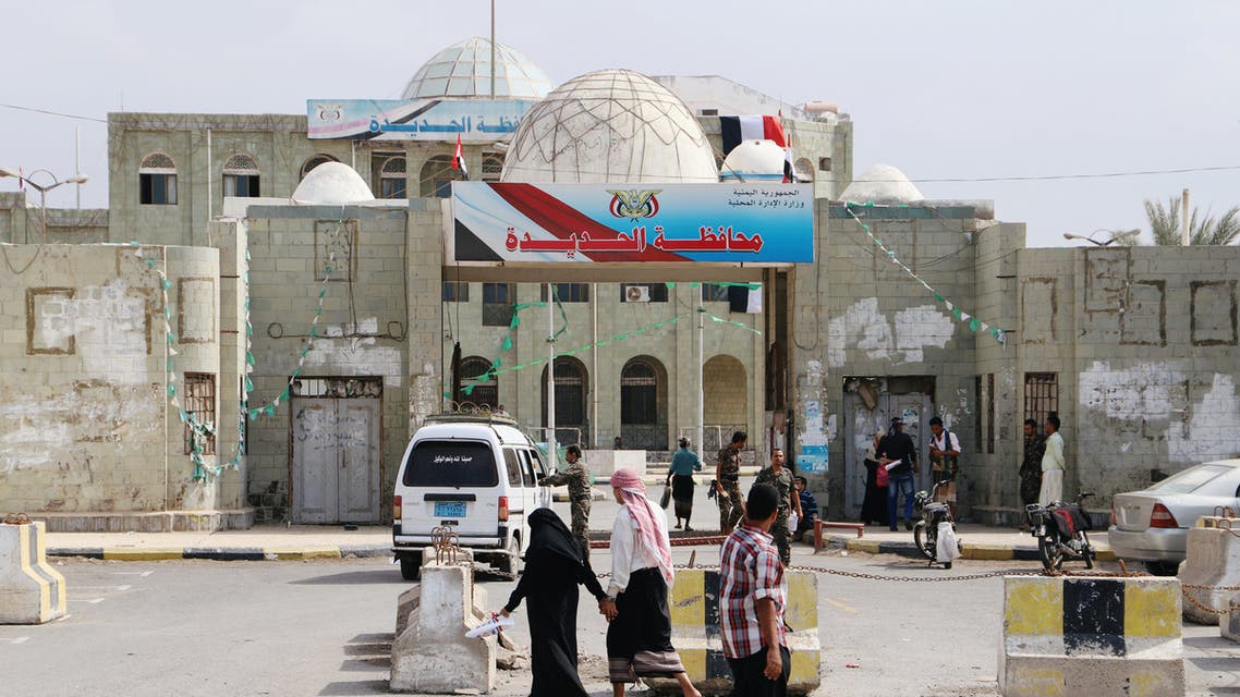 People walk past the headquarters of municipality of the Red Sea port city of Hodeidah, Yemen February 13, 2019. REUTERS/Abduljabbar Zeyad