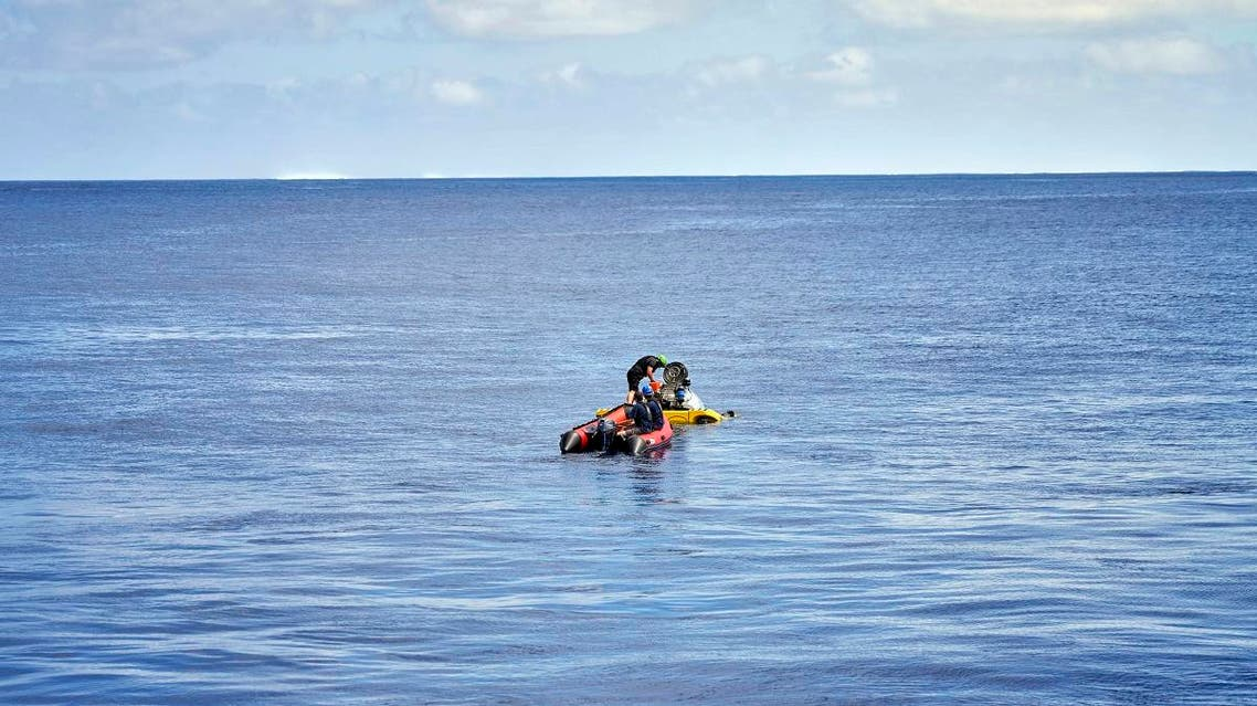 A small boat carrying Stephanie Marie, a young scientist from the Seychelles, reaches a submersible for a technical test dive near the tiny Alphonse atoll. (AFP)