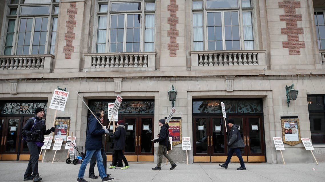 Members of the renowned Chicago Symphony Orchestra carry signs as they strike on March 11, 2019 in Chicago, after 11 months of pay talks failed to reach an agreement. The musicians say the company is asking them to reduce overall salary and benefits despite increasing revenue from sales and donations.