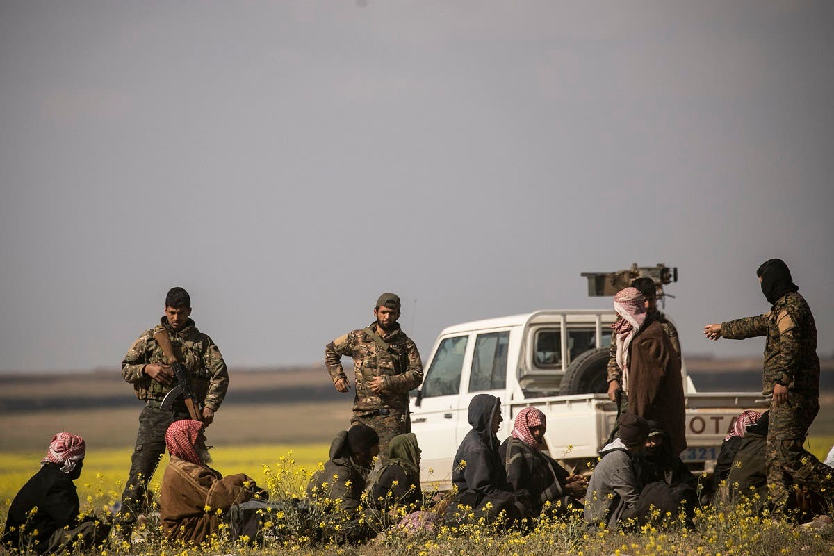 Men suspected of being ISIS extremist fighters arrive at a screening point run by US-backed Syrian Democratic Forces. (AFP)