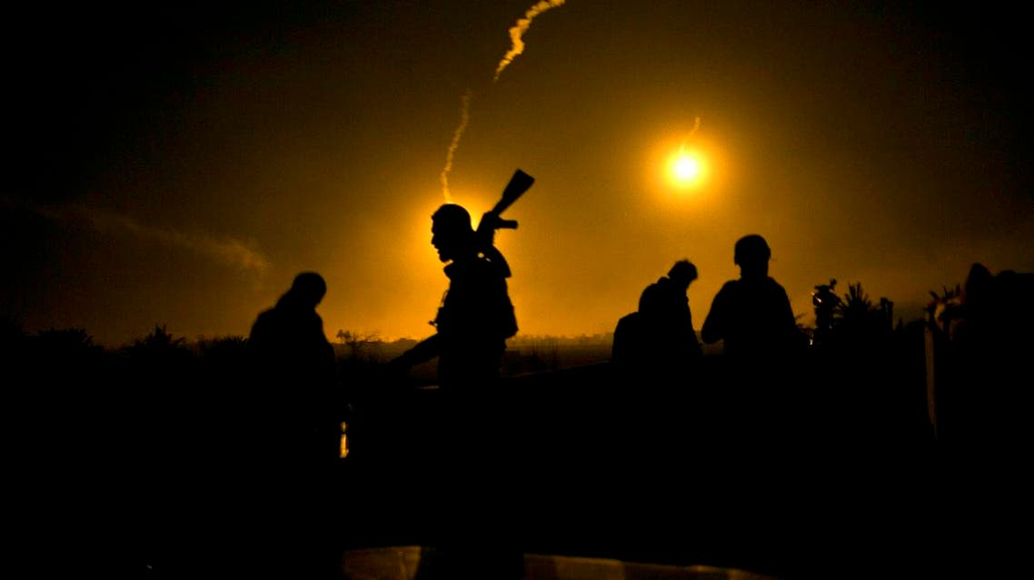 A US-backed Syrian Democratic Forces (SDF) fighter watches illumination rounds light up Baghouz, Syria, as the last pocket of ISIS is attacked on March 12, 2019. (AP)