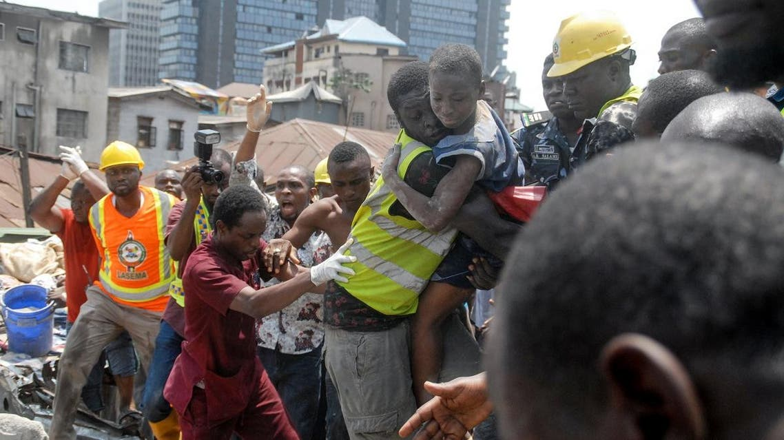 Emergency personnel rescue a child at the site of a building which collapsed in Lagos on March 13, 2019. (AFP)