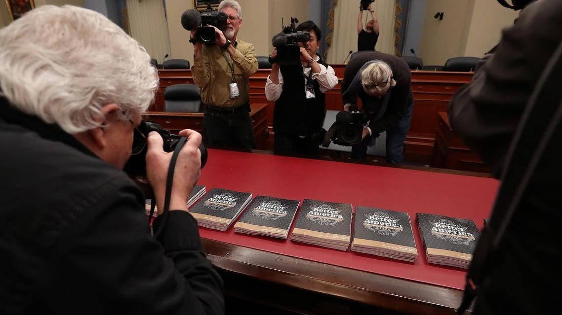 Members of the media gather around copies of volume 1 of President Donald Trump's new budget for 2020 that has been delivered to the House Budget Committee in Washington, DC. (AFP)