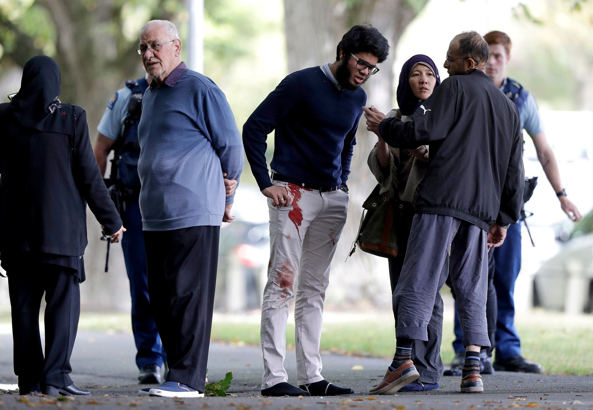 People stand across the road from a mosque in central Christchurch on March 15, 2019. (AP)