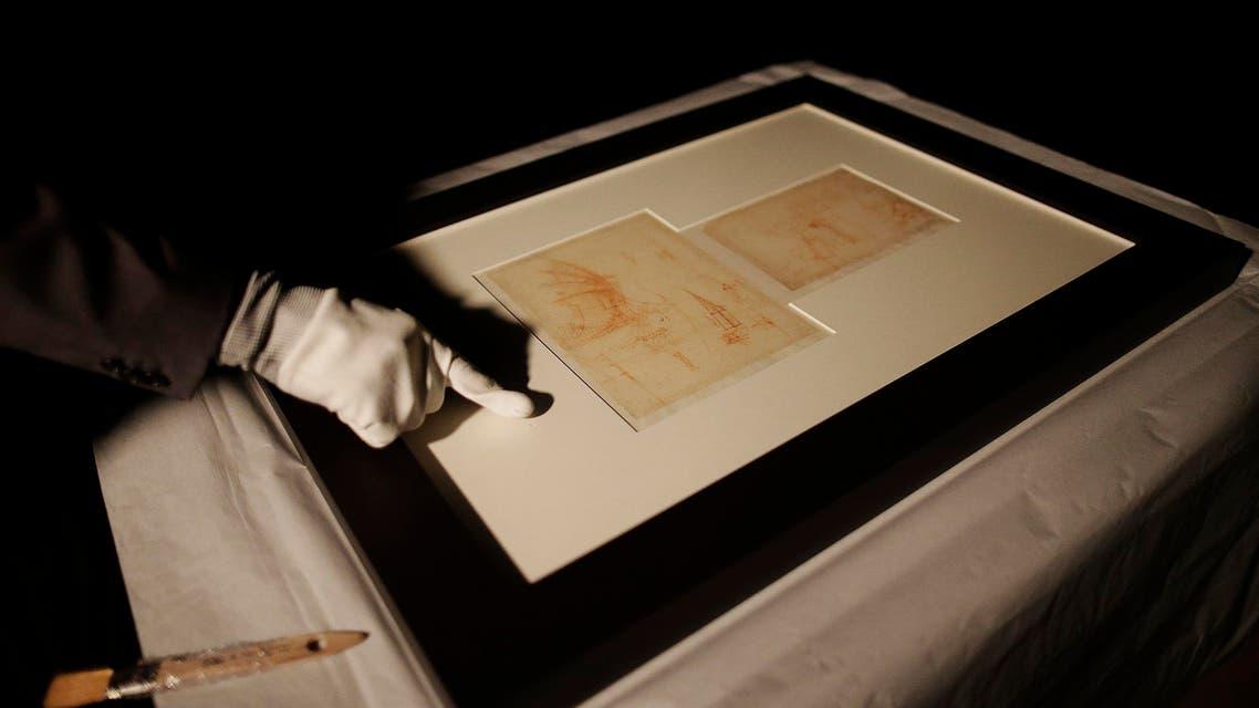 "A representative from the Veneranda Biblioteca Ambrosiana in Milan, inspects an original drawing titled ""Mechanical Wing"" from the Codex Atlanticus by Leonardo da Vinci  (AP)"