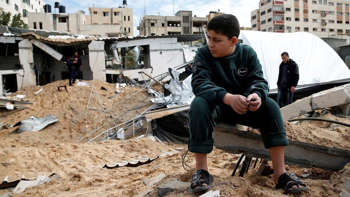 A Palestinian boy sits next to the destroyed Hamas site following Israeli air strikes, in Gaza City March 15, 2019. (Reuters)