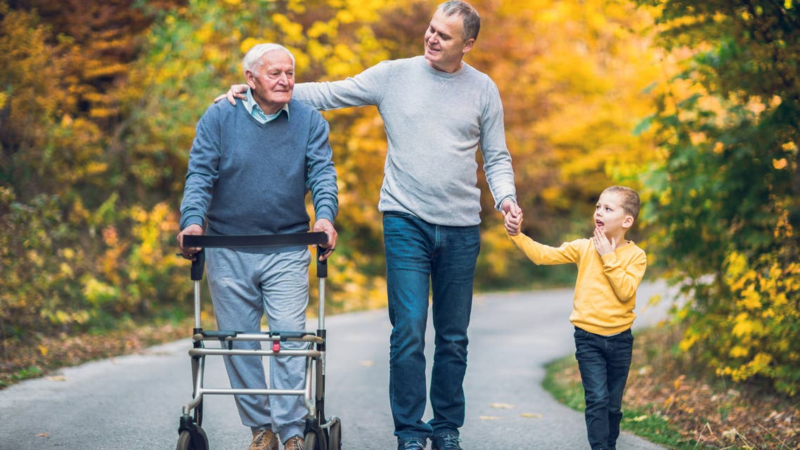 Elderly father adult son and grandson out for a walk in the park. - Stock image