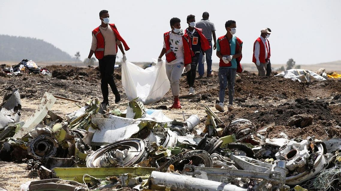 Ethiopian Red Cross workers carry a body bag with the remains of Ethiopian Airlines Flight ET 302 plane crash victims at the scene of a plane crash. (Reuters)