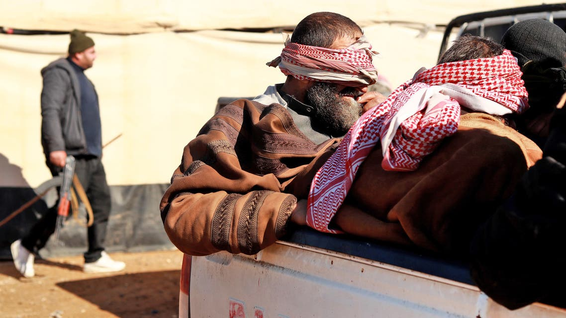 Alleged Islamic State (IS) group fighters who fled from the frontline Syrian village of Baghuz, near the Iraqi border, sit blindfolded in the back of a pickup truck after being taken into custody by SDF forces for screening, near the Omar oil field in the countryside of the eastern Syrian Deir Ezzor province on January 30, 2019.