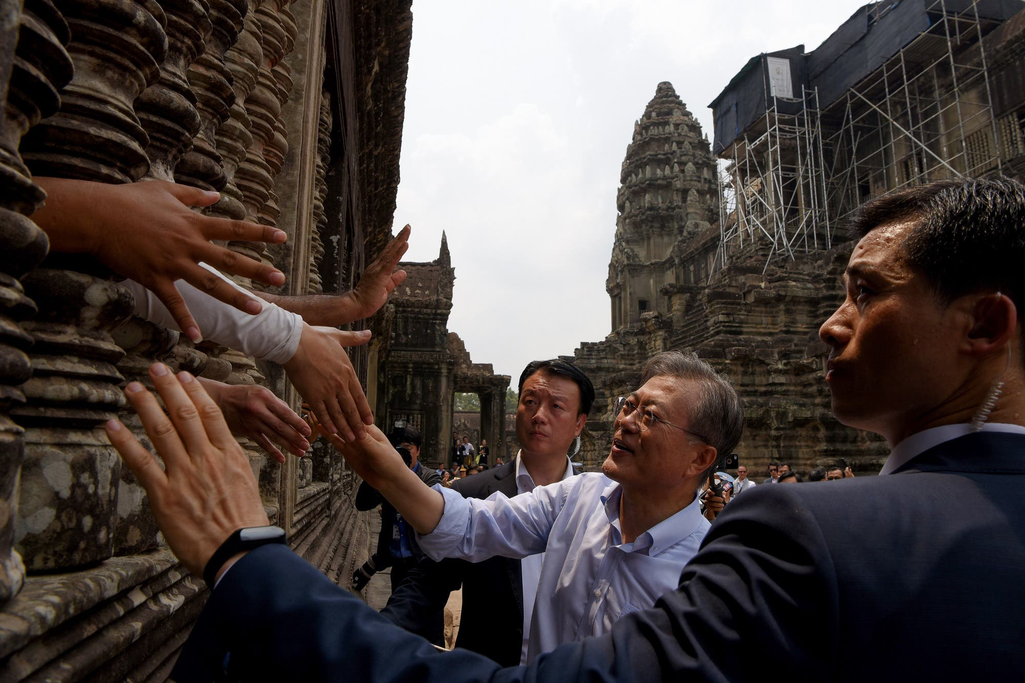 South Korea's President Moon Jae-in shakes hands with tourists during his visit to Angkor Wat temple in Siem Reap province on March 16, 2019. (AFP)
